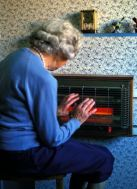 A693C0 elderly lady holding her hands near an electric fire